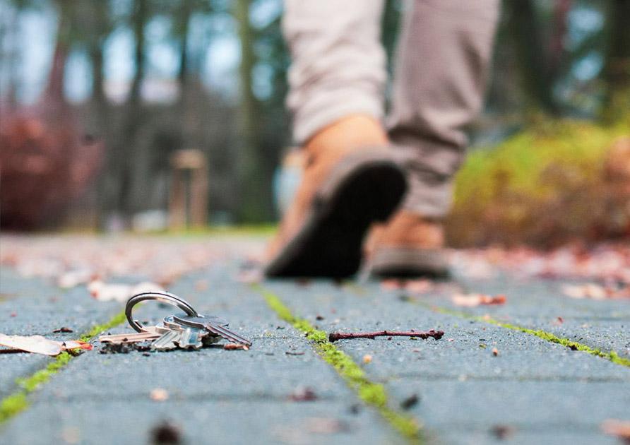 En förlorad nyckelknippa med nycklar som ligger på marken. En person ses gående därifrån i bakgrunden. Med SST Nyckelbricka hittar 9 av 10 borttappade nycklar hem igen!