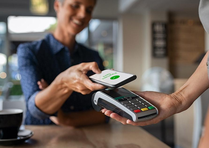 En kund betalar med mobilen genom att hålla den över en betalterminal som säljaren håller i. Utöver att betala med mobilen kan du även skydda dig med RFID Skyddskort för att undvika skimming av ditt betalkort.