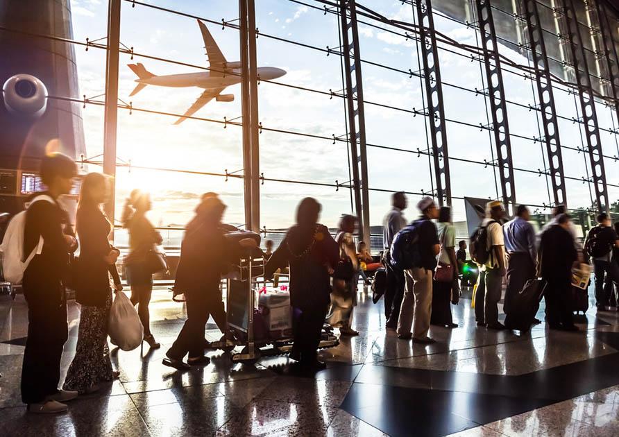 Människor med bagage i olika former står i kö på en flygplats. I bakgrunden flyger ett flygplan förbi. Med SST ID Världsbricka får du förseningsersättning i samband med flygresor!
